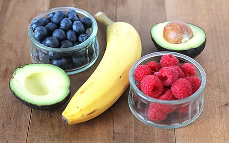 A selection of smoothie ingredients: avocado, blueberries, bananas and raspberries.