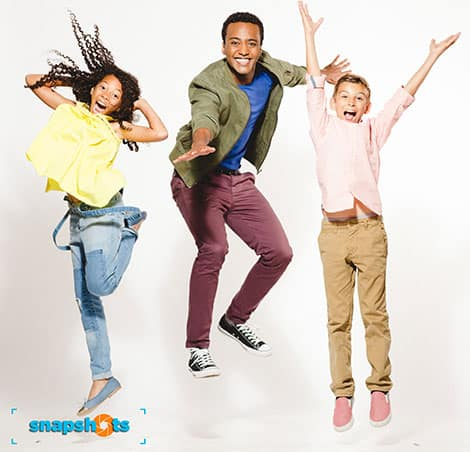 The host of Snapshots with two kids, jumping for joy.