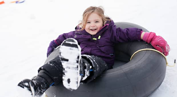 a young child gleefully plays in the snow