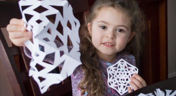 young girl holding paper snowflakes