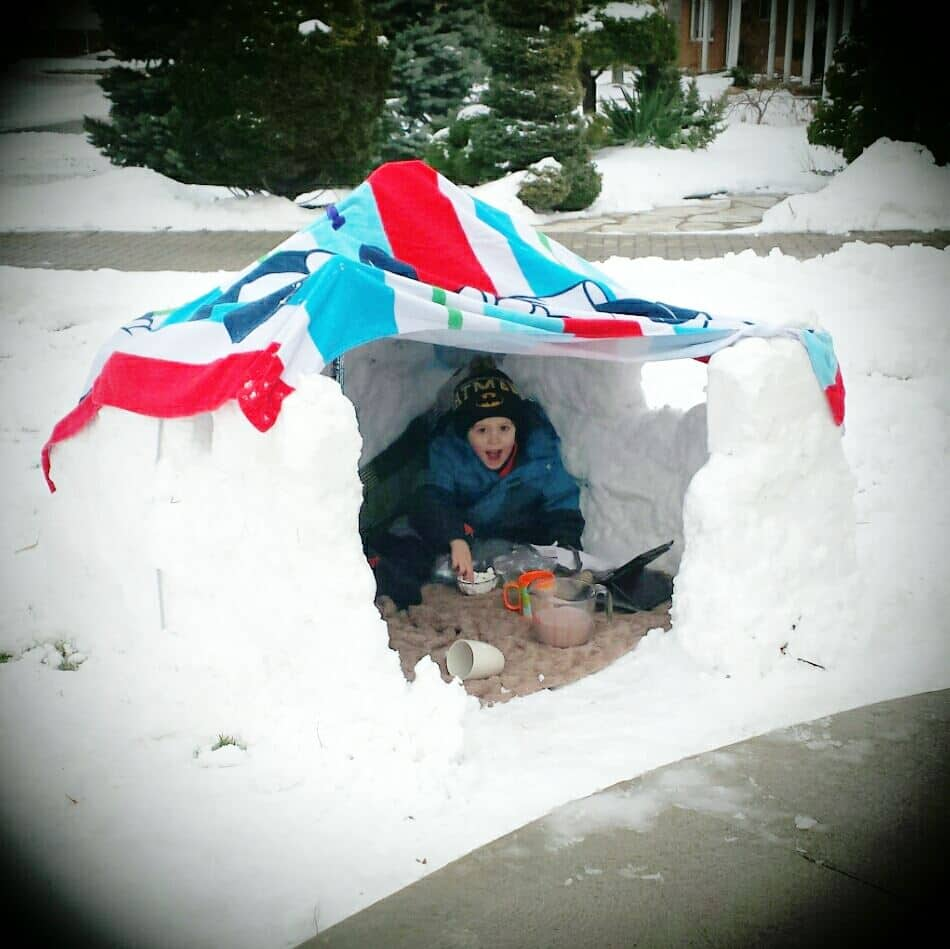 A kid watches a tablet in a snow fort.