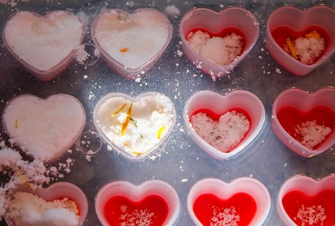 packing the mixture into a heart-shaped tray to make bath bombs