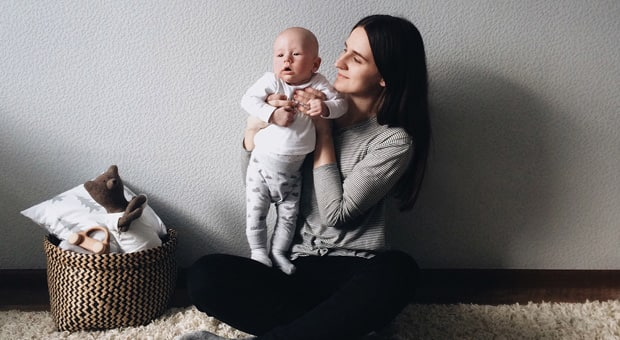 A teen mom with her baby sitting cross-legged on the floor