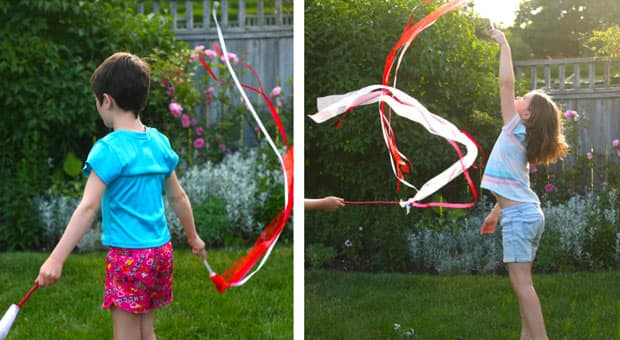 Two children playing with the ribbon twirlers in a backyard. The twirlers are painted sticks with red-and-white ribbons attached. They flutter and fly as kids wave them through the air.