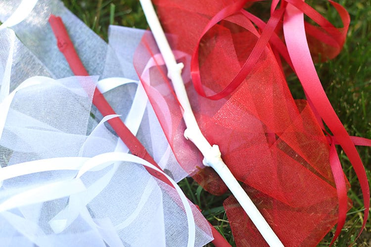 Painted sticks and cut lengths of ribbon, lying on the grass ready to go.
