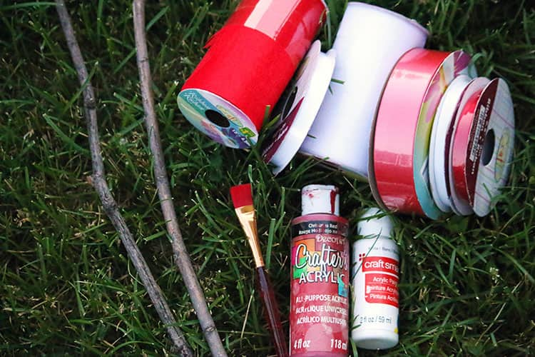 Craft supplies sitting on grass. There are three different widths of both the red and white ribbon.