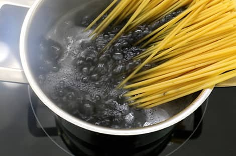 Spaghetti noodles cooking in black liquid.