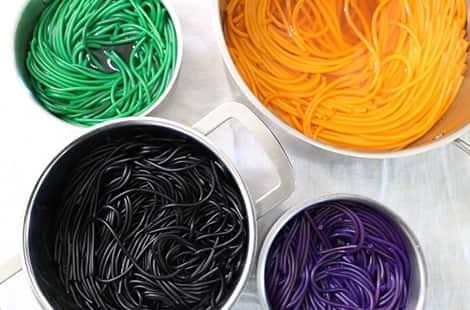 Green noodles, orange noodles, purple noodes and black noodles all in pots.