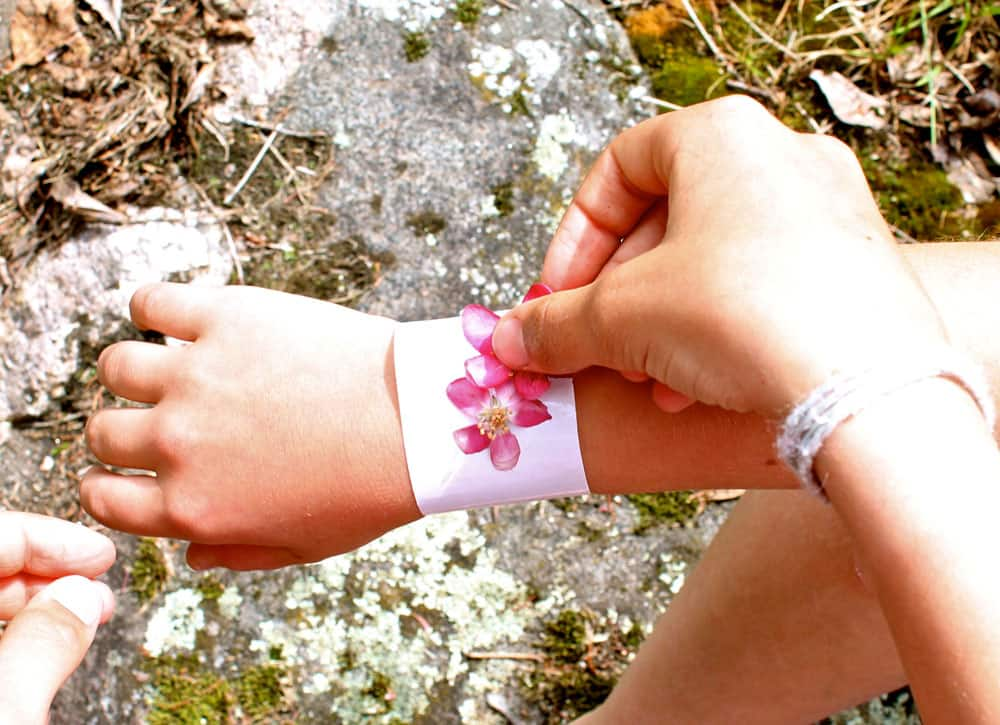A child sticks pink flowers on the sticky side of duct tape.