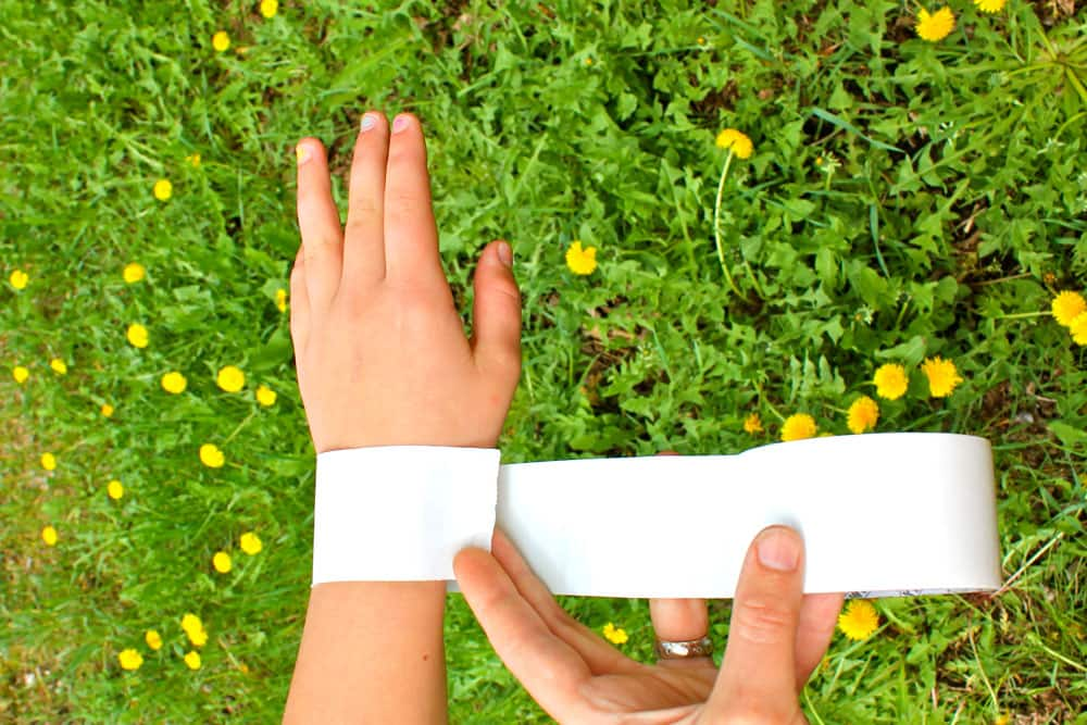 A child's wrist wrapped with sticky-side out duct tape.