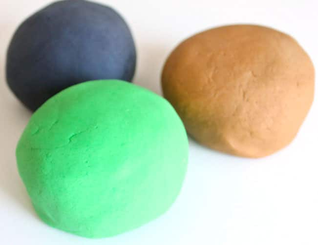 Three balls of finished play dough: black, brown and green.