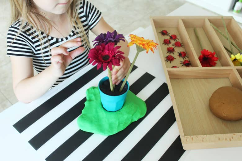 A young girl placing a faux flower into a pot filled with black play dough.