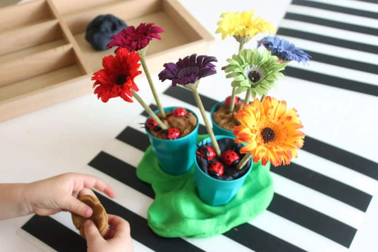 Three pots filled with brown and black play dough, faux flowers and plastic lady bugs, sitting on a