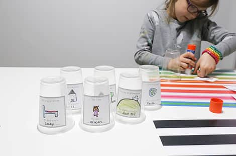 Little girl glues cut-outs onto plastic cups.