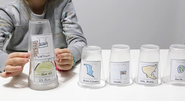 Child stacks cups.