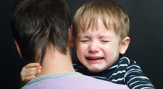 Parent holds crying child.