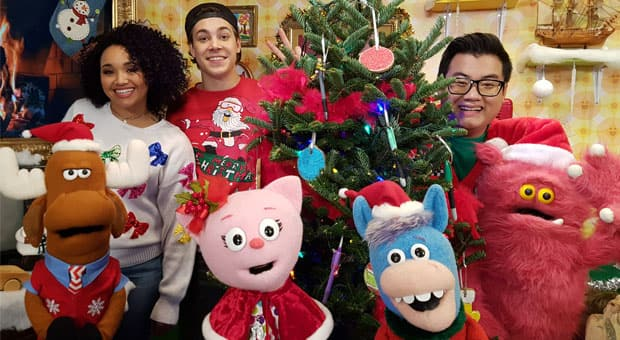 The hosts of Studio K crowd together around a Christmas tree.