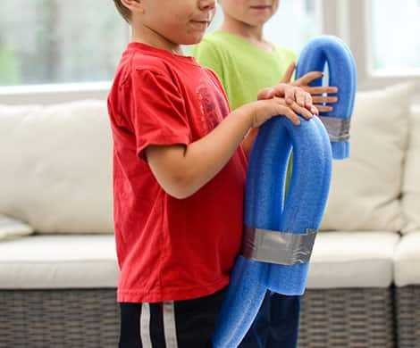Two kids hold their pool-noodle horses.