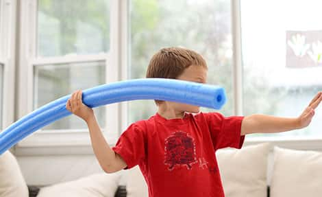 A child holds a pool noodle like a javelin and is about to throw.