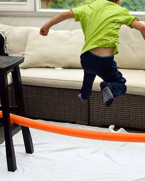 A pool noodle is suspended between two stools, about a foot off the ground. A young child is jumping over it.