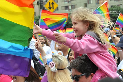 A smiling girl sitting on a man's shoulder's in a crowd with lots of rainbow flags flying around her.