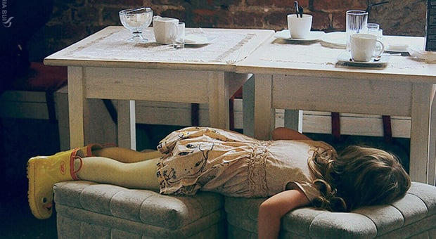 Child lies across benches in a restaurant