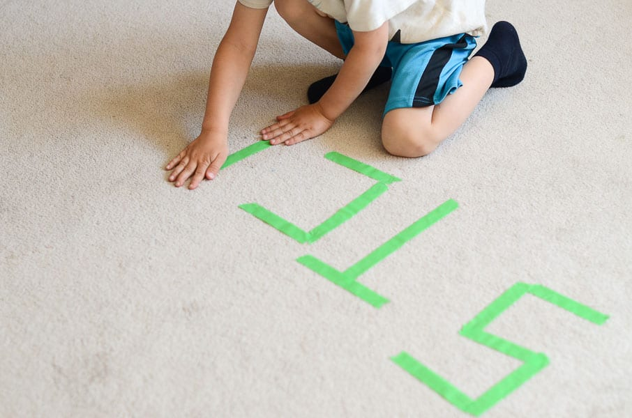 A child writes the word