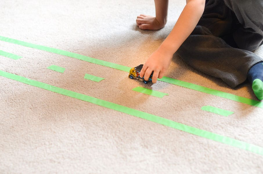 A kid plays with a toy car on a road made out of tape.