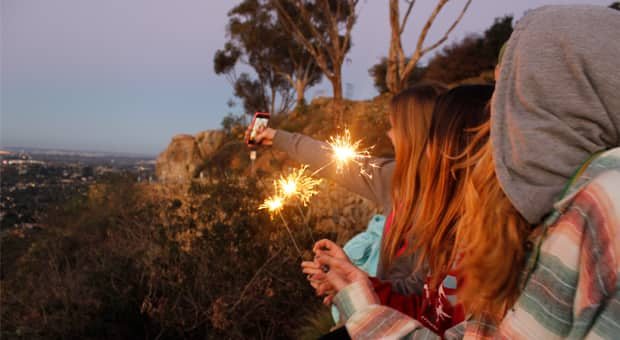 three teen girls with sparklers taking a selfie on the side of a hill