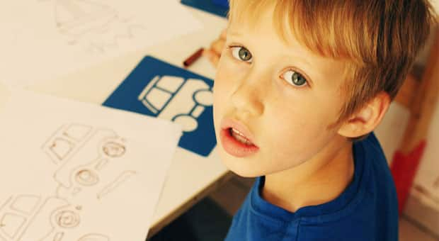 A young boy looking up from his drawing.