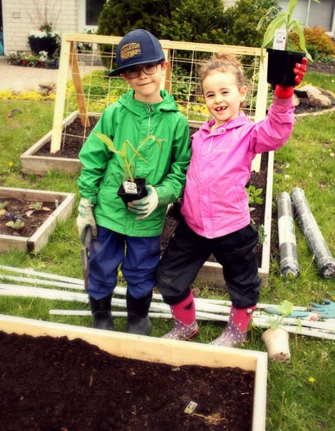 The author's two children standing in their garden with plants.