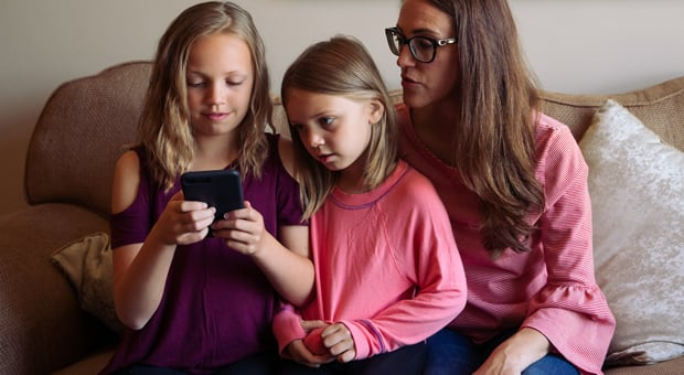 a mother looks at a phone with her children
