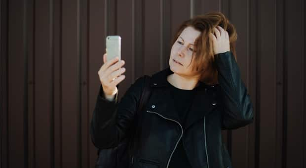 a woman holds up her phone to film herself