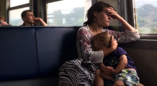 Woman with child in her lap holds her head