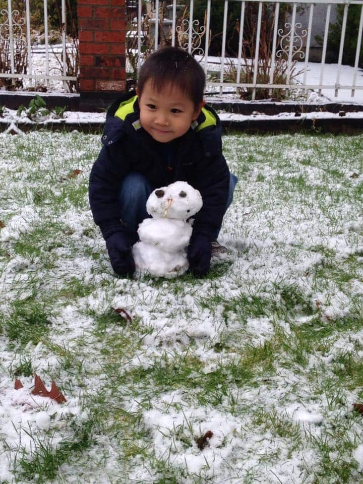 A boy crouches with a tiny snowman.