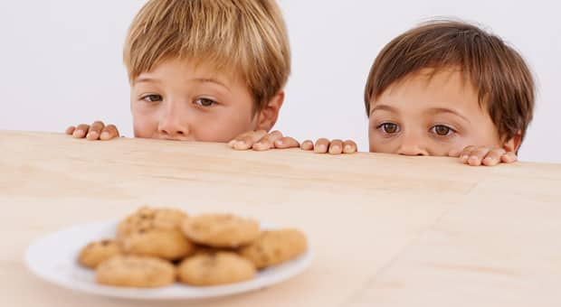 Two kids peering over the edge of the table at a plate of chocolate-chip cookies.
