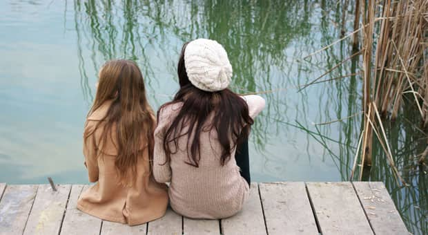 A mother and daughter sitting on a dock looking out over a pond.