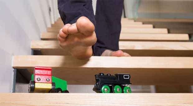 a dad is about to step on a toy train
