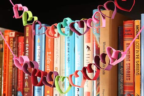 a colourful toilet paper roll heart garland hanging on a bookcase