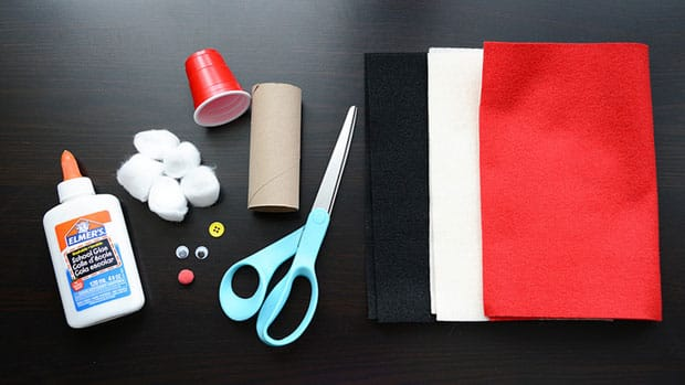 Using your scissors, cut a piece of red felt about two thirds the height of your toilet paper roll. Place some glue on it and wrap it ...