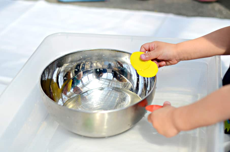 A child holds two yellow circles over a metal bowl filled with water.
