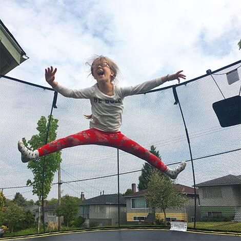 Child jumps on trampoline.