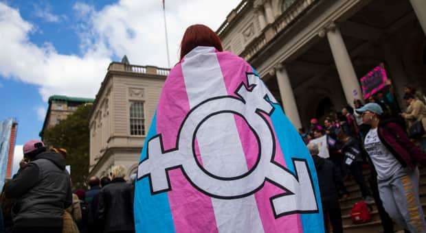 A supporter wears a trans flag as a cape at a march