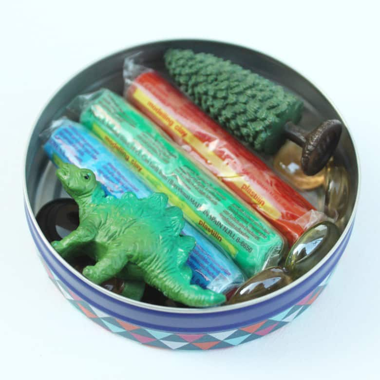 A tin filled with plasticine and a dinosaur toy.