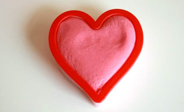 Pink play dough in a heart-shaped cookie cutter.