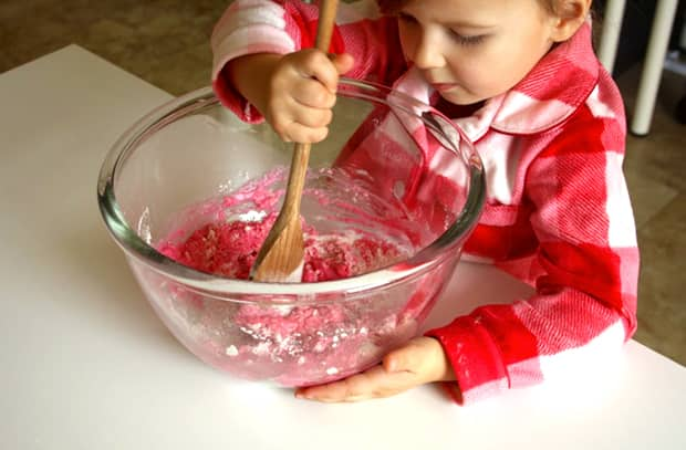 A girl stirs pink play dough.