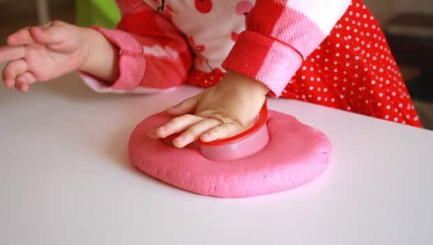 A girl presses pink play dough into a disc.