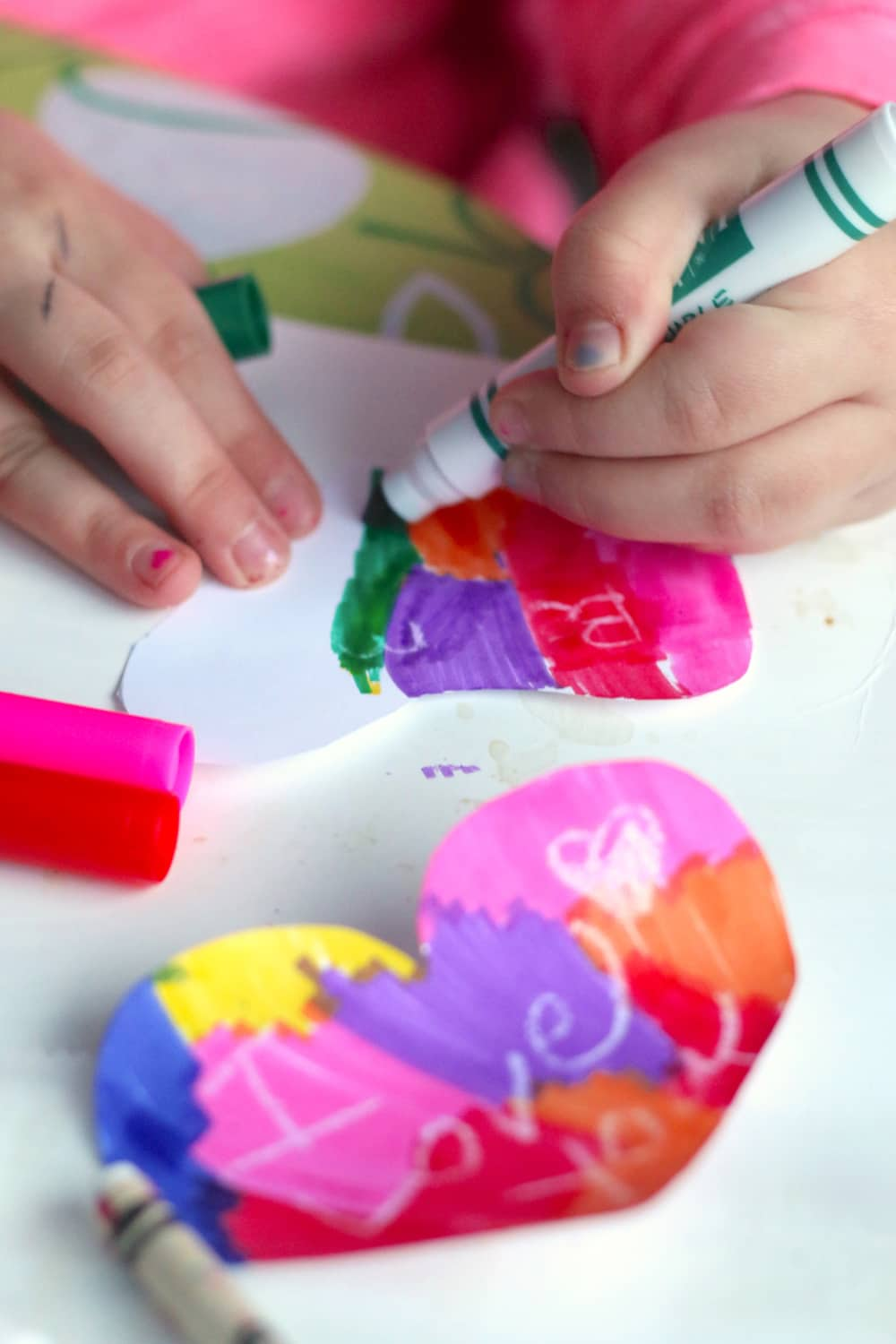 A child colours with bright washable markers.