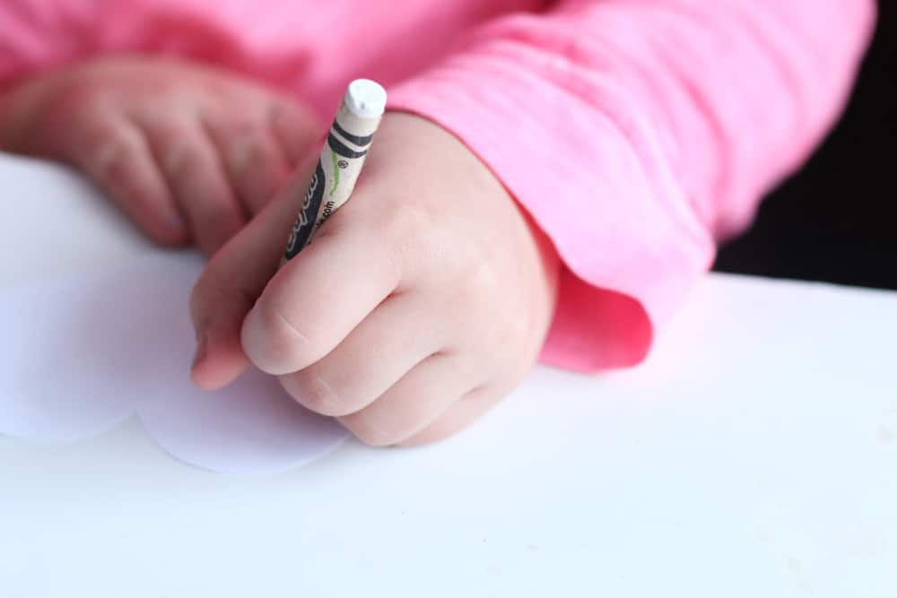 A child draws on white paper with a white crayon.