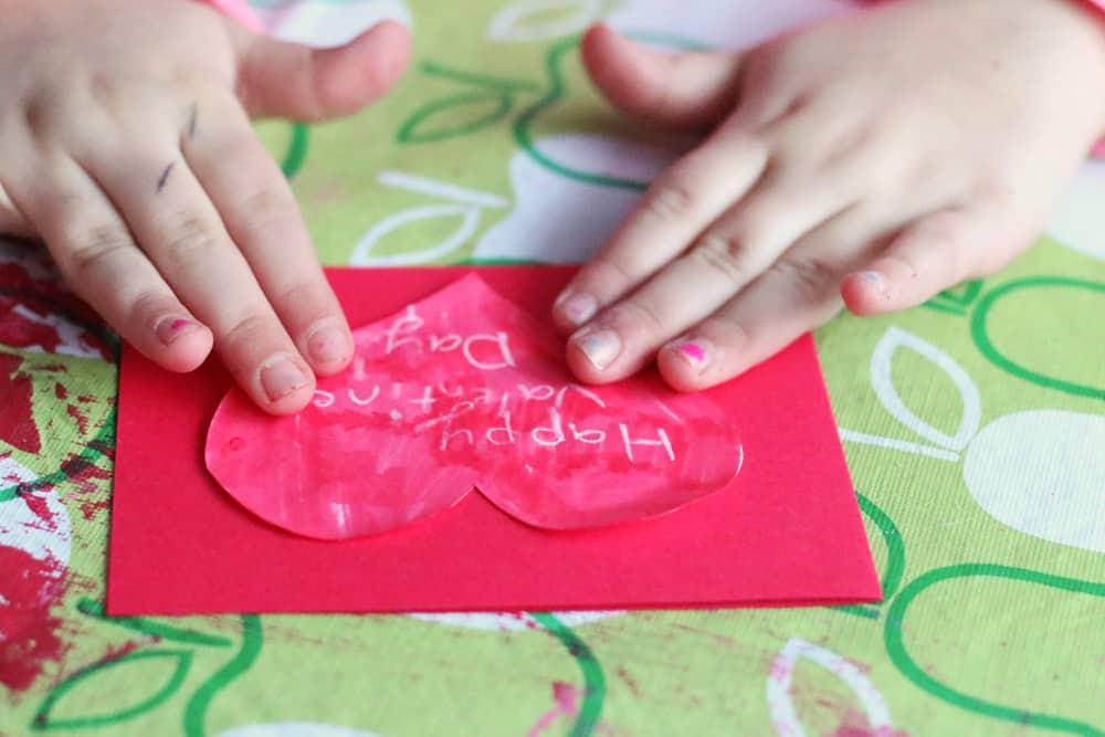 A child glues a heart onto a colourful card.